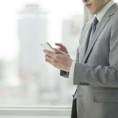 The businessman who operates a smartphone